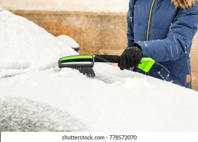Woman removing snow from snow covered car in snowfall