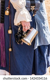 Woman at Renaissance Fair dressed in period clothing and carrying a pewter drinking mug for ale or mead.