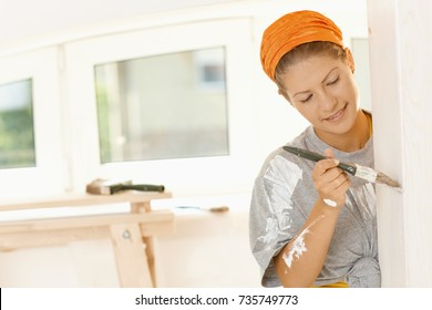 Woman renewing home. Happy young woman painting wall with paint brush in her fixer upper, smiling.