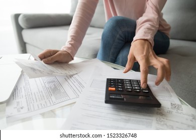 Woman renter holding paper bills using calculator for business financial accounting calculate money bank loan rent payments manage expenses finances taxes doing paperwork concept, close up view