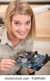 woman repairing an electronic component