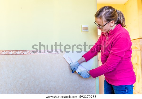 Woman repairing a wall in apartment, concept of home renovating by individual people