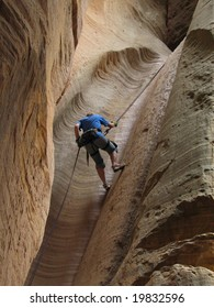 Woman repelling in a slot canyon near Zions National Park.