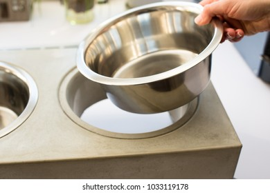 Woman replacing the bowl of a stylish dog food bowl station made out of concrete in the kitchen