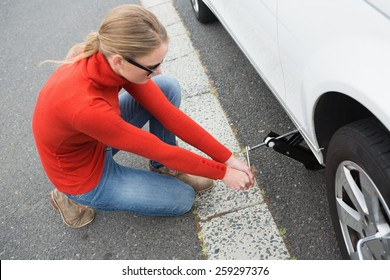 Woman replacing tire of her car