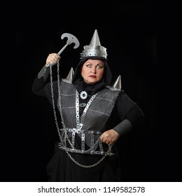 Woman represents an Asian warrior armed with cold steel on black background