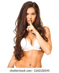 Woman requires silence. Young beautiful brunette has put forefinger to lips as sign of silence, isolated on white