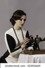 Woman resembling Coco Chanel sitting at a sewing machine