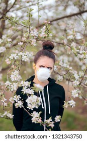 Woman with Respirator Mask Fighting Spring Allergies. Funny girl trying to protect herself from pollen and allergens