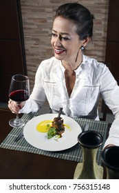 Woman in restaurant drinking red wine, haute cuisine