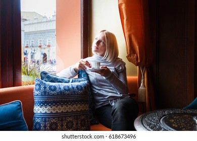 A woman is resting in a cafe and enjoying the view outside the window while drinking a cup of coffee. The blonde girl relaxes in her free time.
