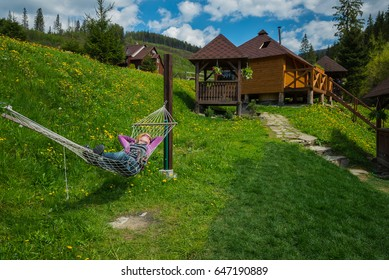 a woman resting in the hammock  in the mountains. wooden houses on the background and the green grass