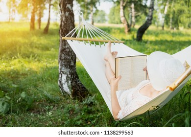 Woman resting in hammock outdoors. Relax and reading the book