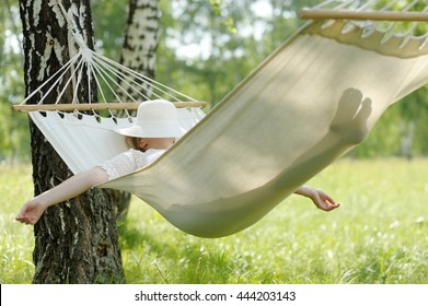 Woman resting in hammock outdoors. Sleeping outdoors.
