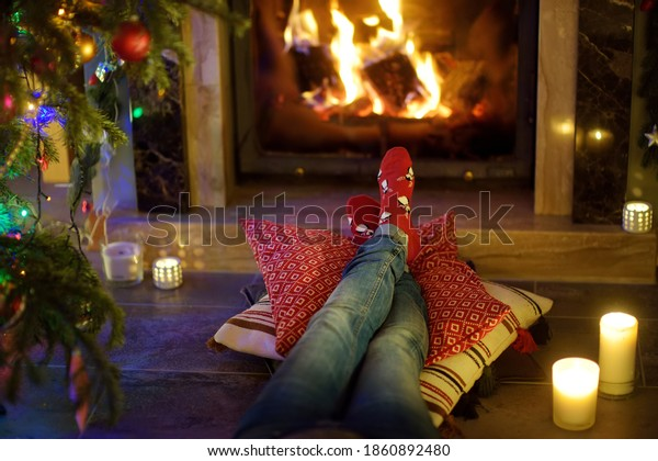 Woman resting her legs in red festive socks in a room with a burning fireplace and candles on cozy Christmas evening. Happy festive time in winter.