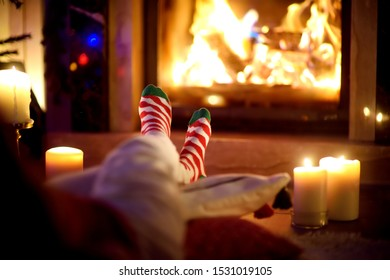 Woman resting her legs in striped festive socks in a room with a burning fireplace and candles on cozy Christmas evening. Happy festive time in winter.