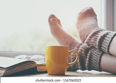 Frauen, die sich auf dem Tisch mit Morgenkaffee die Beine in warmen Socken halten und Buch lesen
