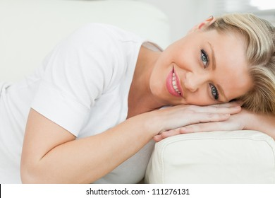 Woman resting on an armrest of sofa