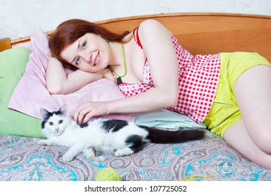 Woman resting on a bed with a kitten