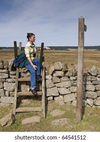 A woman resting on a crossing stile at Hadrians Wall