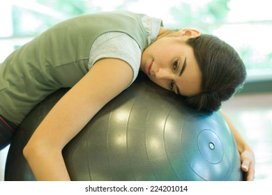Woman resting on fitness ball