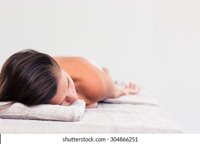Woman resting on massage lounger in a wellness center isolated on a white background