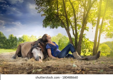 Woman resting on shoulder of lying horse, under tree in sunset . Horsemanship . Humane attitude to the horse. Village scene. Outdoor nature landscape