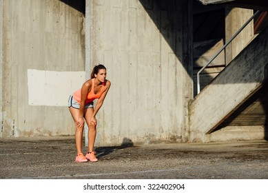 Woman resting and taking a break after running and exercising. Fitness and healthy lifestyle concept.