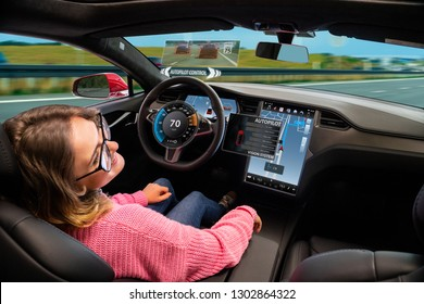 A woman resting while her car is driven by an autopilot. Self driving vehicle concept