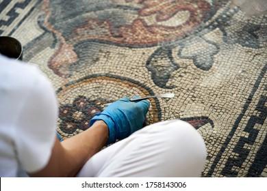 woman restoring an ancient mosaic