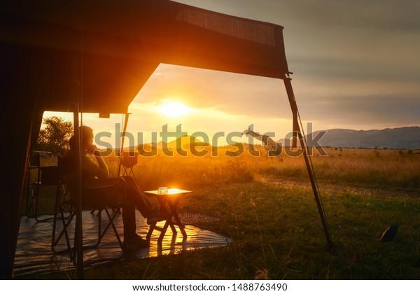 Une femme se repose après un safari sous une tente de luxe au coucher du soleil, dans la savane africaine du Parc National du Serengeti, en Tanzanie.Femme Camping Tente Savanna Concept extérieur