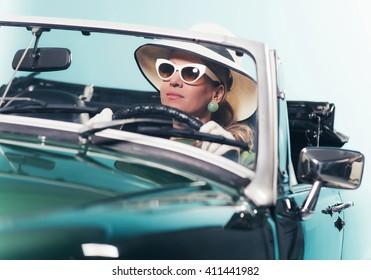 Woman in retro 1960s fashion with hat and shades driving convertible.