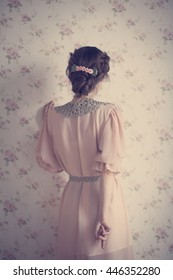 Woman in retro dress with a vintage hairstyle is back on the background wall with floral pattern