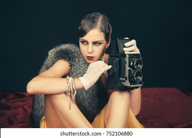 Woman with retro hair, makeup and old camera. beauty, retro look, pinup fashion.