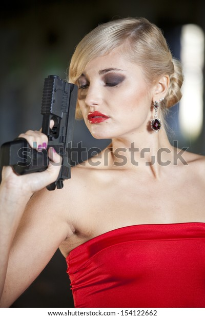 woman in retro look holding a handgun close to her face in thinking position