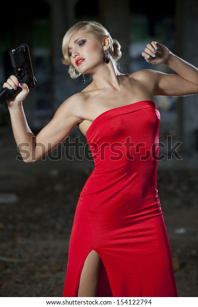 Woman in retro look playing a scene where she has been shot from a gun