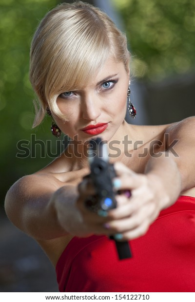 Woman in retro look pointing a gun at the camera