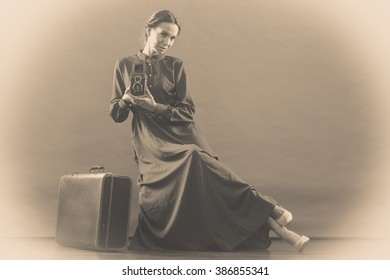 Woman retro style long dark gown old suitcase and camera taking picture, vintage photo sepia tone
