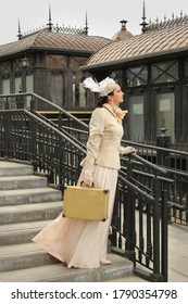 a woman at a retro train station. a girl in a historical costume of the 19th  with a suitcase