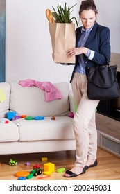 Woman returned home from shopping and looking at the mess in the room