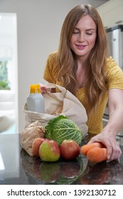 Woman Returning Home From Shopping Trip Unpacking Plastic Free Grocery Bags