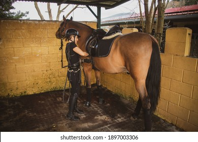 woman rider dressed in black and with a black hoof in the stable un saddling her horse