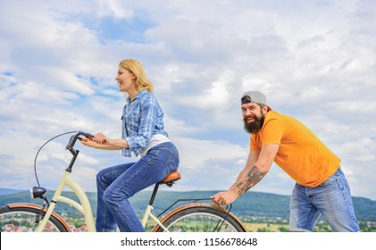 Woman rides bicycle sky background. Push and promoting. Impulse to move. Man pushes girl ride bike. Support helps believe in yourself. Feel impulse to start moving. Girl cycling while man support her.