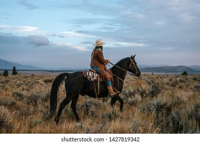 Woman rides her black horse through a field of sagebrush at sunset or sunrise in Jackson Hole, Wyoming