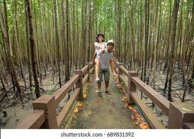 Woman riding back man on walkway bridge in mangrove forest