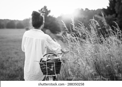 Woman riding bicycle with the basket of fresh food. Black and white photography.