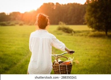 Woman riding bicycle with the basket of fresh. Color toned image.