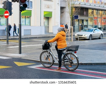 Woman riding bicycle and crossing road street of Ljubljana old town, Slovenia. People on bike and cycle in Slovenian city view in winter. Cyclist and road landmark. Urban green capital.