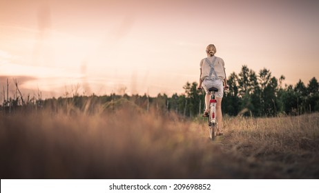 Woman riding a bicycle down a rural road