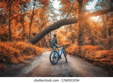 Woman riding a bicycle in  forest in autumn at sunset. Colorful landscape with sporty girl with backpack riding a mountain bike, dirt road, trees with orange leaves  in fall. Sport and travel. Cycle